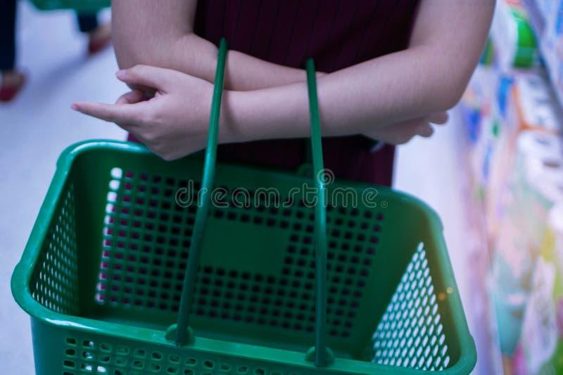 Tragendes grünes Einkaufen des Korbes der jungen Frau stockbild