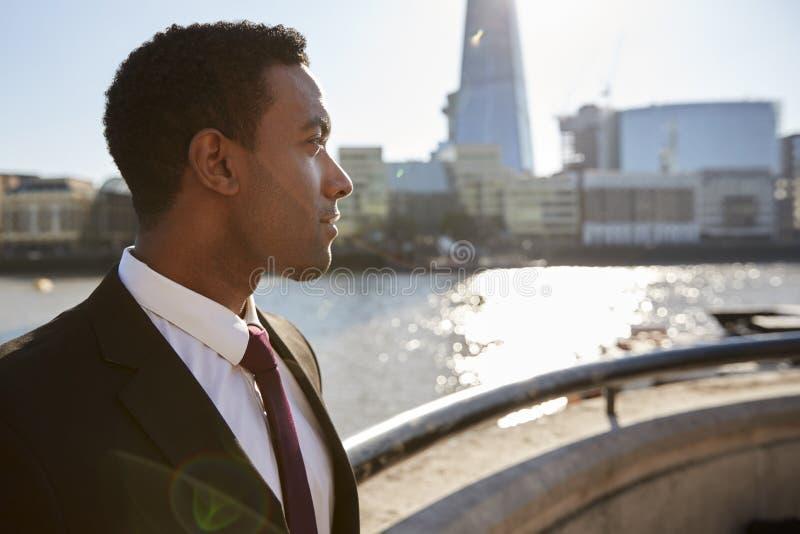 Tragendes Hemd und Bindung des jungen schwarzen Geschäftsmannes, welche die Themse, London, weg schauend bereitsteht, hintergrund lizenzfreie stockbilder