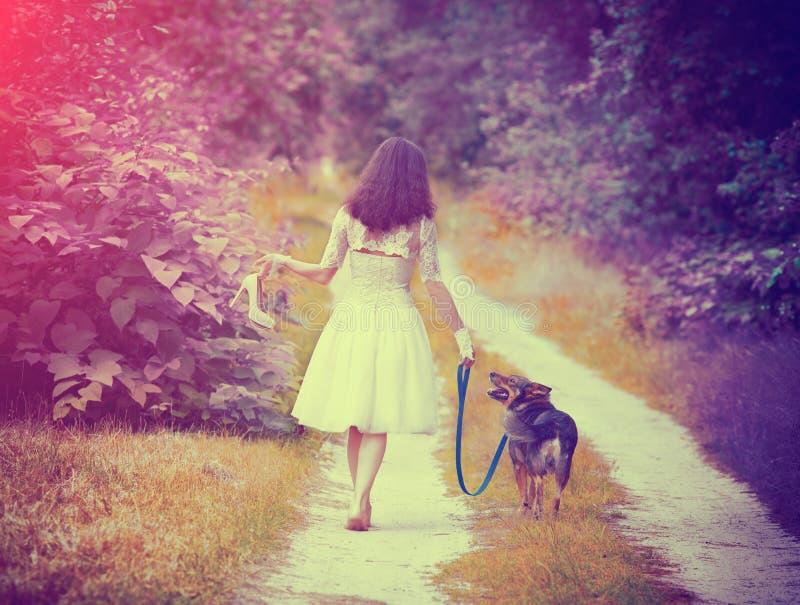 Tragendes Hochzeitskleid der jungen Braut, das barfuß mit Hund geht stockbilder