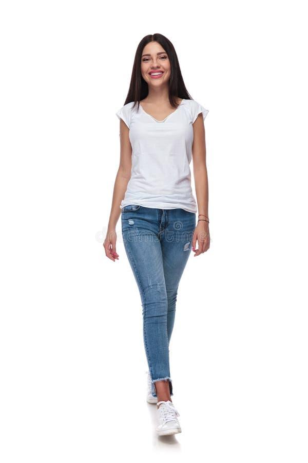 Tragendes Jeansgehen der frohen zufälligen Frau lizenzfreie stockfotografie