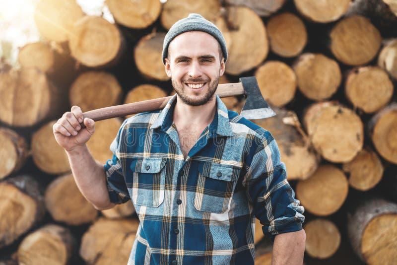 Tragendes kariertes Hemd des starken bärtigen Holzfällers hält Axt auf seiner Schulter lizenzfreies stockfoto