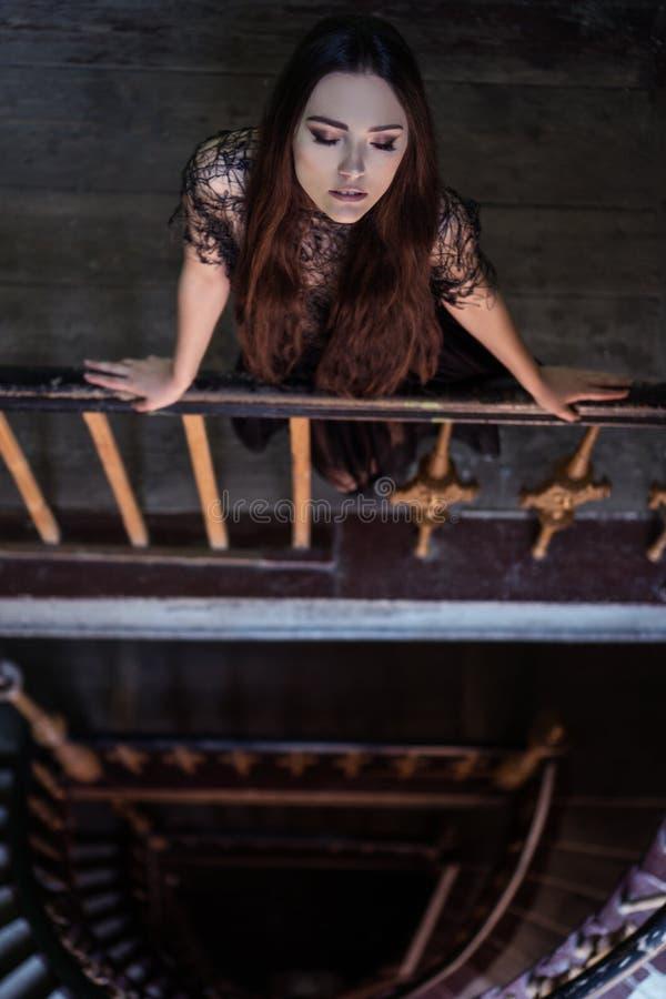 Tragendes Kleid der Frau, das auf dem Treppenhaus - Horrorszene steht stockfotos