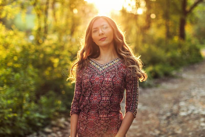Tragendes Kleid der jungen Frau, in der Waldhintergrundbeleuchtung durch Sonnenunterganglicht lizenzfreie stockfotos