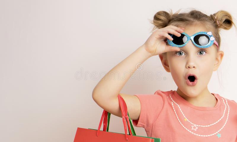 Tragendes Kleid und Sonnenbrille des schönen Mädchens, die Einkaufstaschen halten lizenzfreies stockfoto