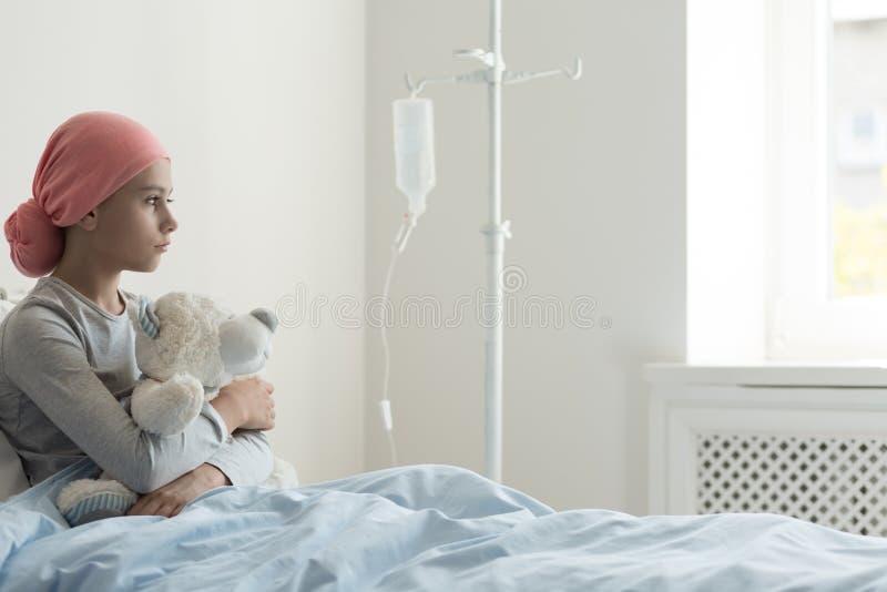 Tragendes Kopftuch des kranken Mädchens und Umarmen des Plüschspielzeugs im Krankenhaus stockbild