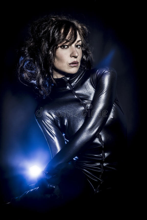 Tragendes Latexkleid der schönen Brunettefrau auf dunklem Hintergrund, stockbild
