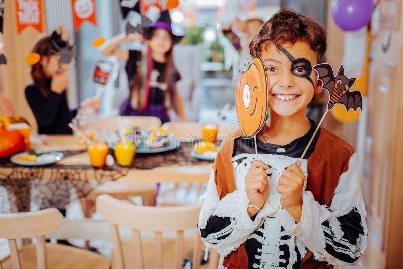 Tragendes Piratenkostüm des dunkelhaarigen Schulmädchens für Halloween, das aufgeregt glaubt lizenzfreie stockfotos