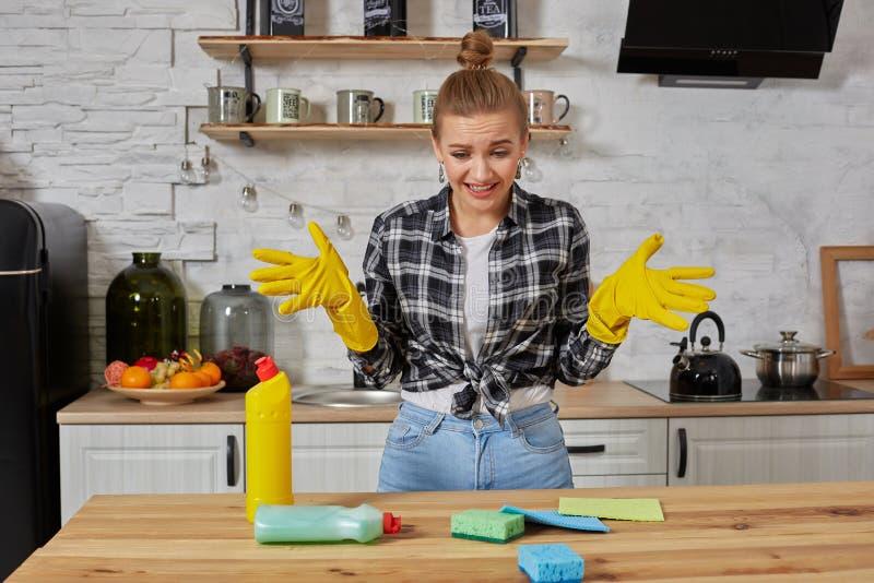 Tragendes Schutzblech der jungen Frau, das zuhause mit Haufen von Reinigungsschwämmen sitzt stockfotografie