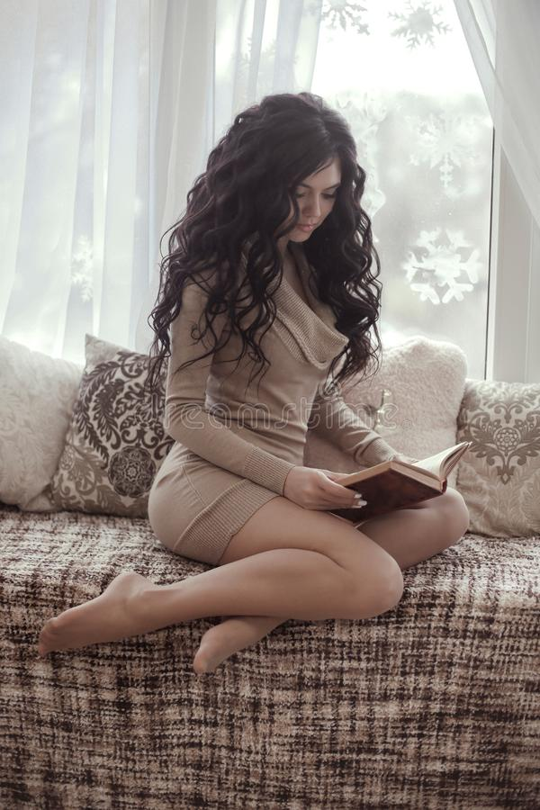 Tragendes Strickkleid der schönen sexy Brunettefrau las den Buh lizenzfreie stockfotografie