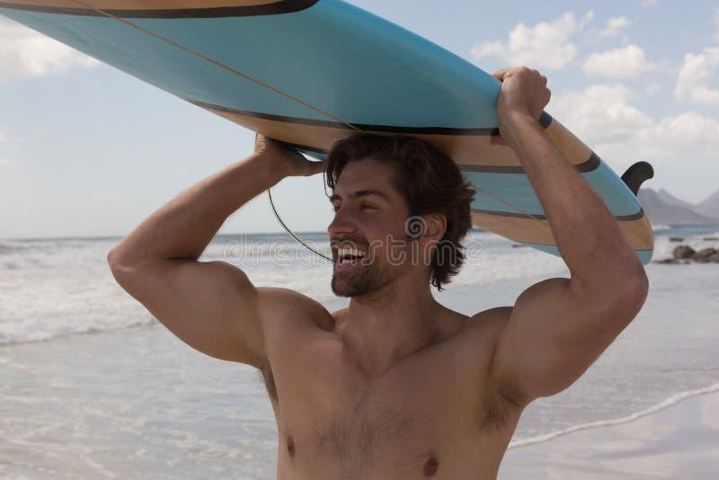 Tragendes Surfbrett des männlichen Surfers auf seinem Kopf am Strand lizenzfreies stockbild