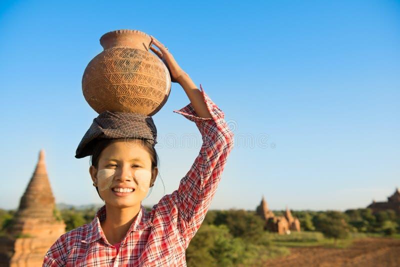 Tragendes Tongefäß des asiatischen traditionellen weiblichen Landwirts auf Kopf lizenzfreie stockfotos