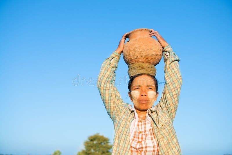 Tragendes Tongefäß des reifen asiatischen traditionellen weiblichen Landwirts auf Kopf stockbilder