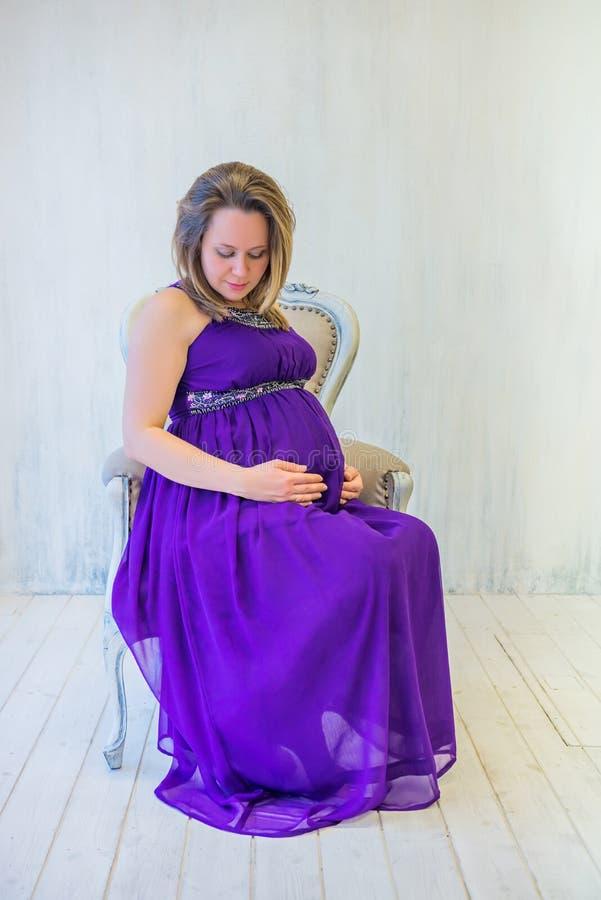 Tragendes ultraviolettes Kleid der schwangeren Frau stockfoto