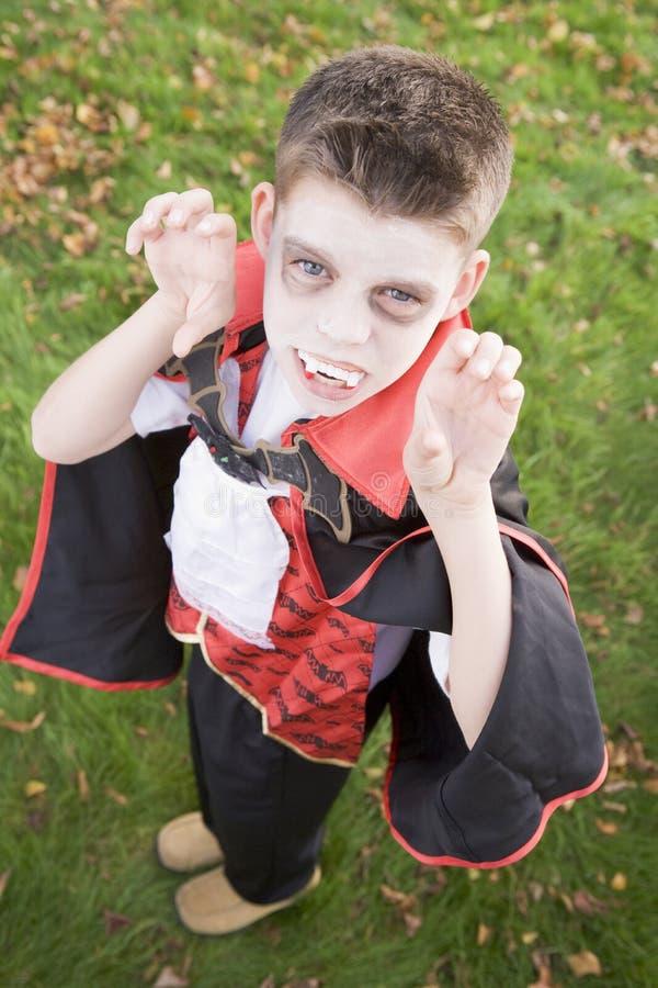 Tragendes Vampirkostüm des jungen Jungen auf Halloween stockbild
