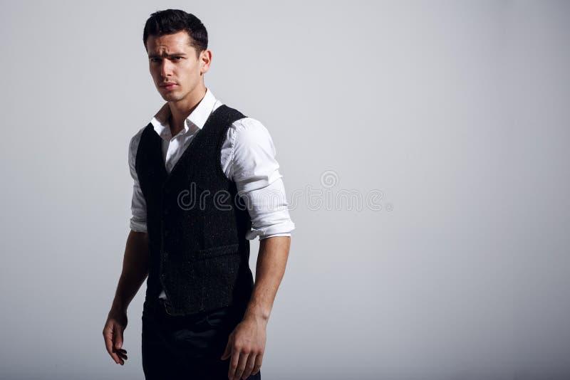 Tragendes weißes Hemd des jungen gut aussehenden Mannes, schwarze Weste, stehend nahe grauer Wand stockfoto