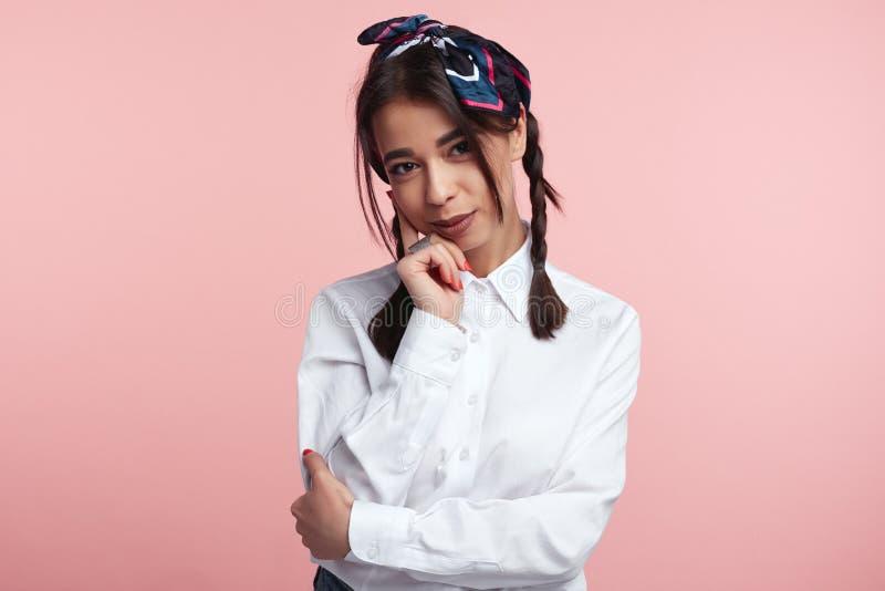 Tragendes weißes Hemd und Stirnband der jungen brunette Frau, die Hand auf Kinn hält und die Kamera, lokalisiert über rosa Wand b lizenzfreie stockbilder