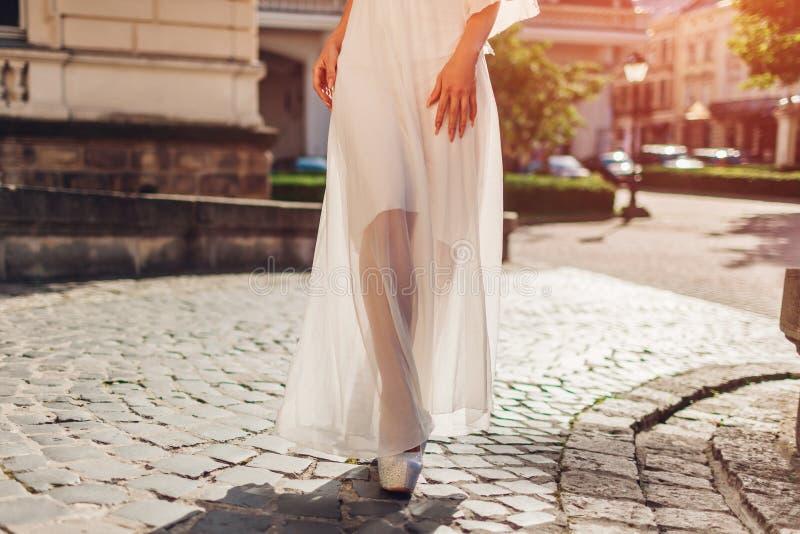 Tragendes weißes Hochzeitskleid der Schönheit draußen im Sommer Dame, die durch Palast bei Sonnenuntergang geht lizenzfreie stockbilder