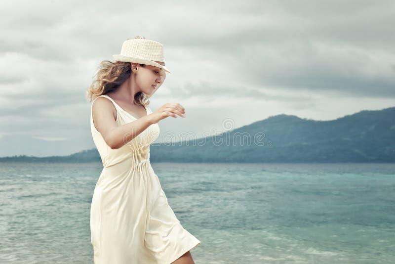 Tragendes weißes Kleid der netten Frau auf einem Strand auf Hintergrund von t lizenzfreies stockbild
