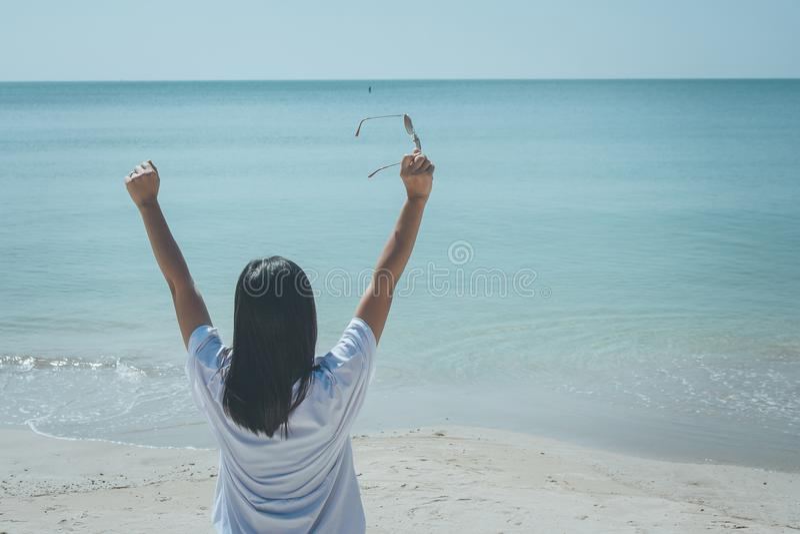Tragendes weißes T-Shirt der Frau, sie stehend auf Sandstrand und Sonnenbrille in ihrer Hand halten, sie das Meer und den blauen  lizenzfreie stockfotos