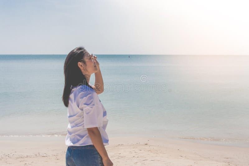 Tragendes weißes T-Shirt der Frau, sie stehend auf Sandstrand und Sonnenbrille mit schöner Meerblickansicht in der Hand halten stockfotografie