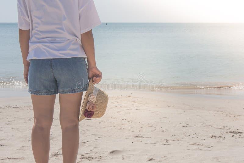 Tragendes weißes T-Shirt der Frau, sie stehend auf Sandstrand und Webarthut in der Hand halten, sie das Meer betrachtend stockbilder
