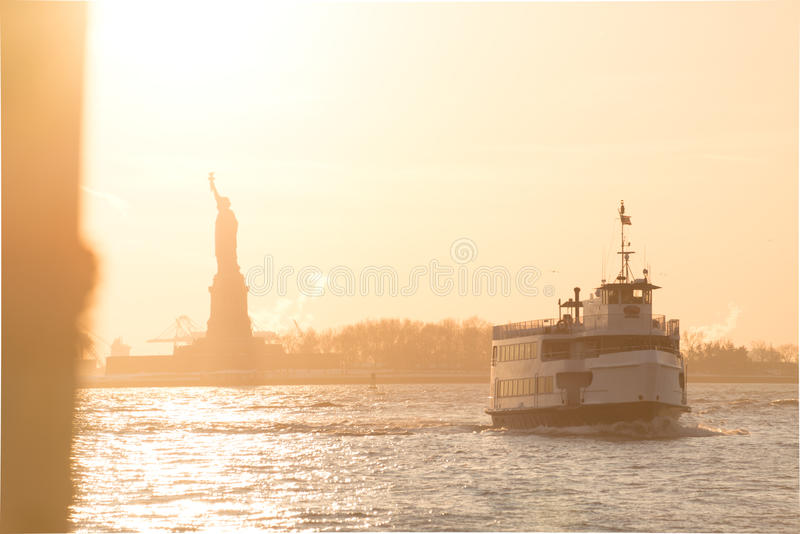 Traghetto e statua della libertà turistici nel porto soleggiato di New York fotografia stock