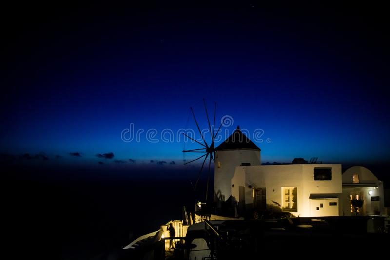 Traiditional greek windmill lit up by artificial lighting during sunset and blue hour. Santorini, Greece. stock image