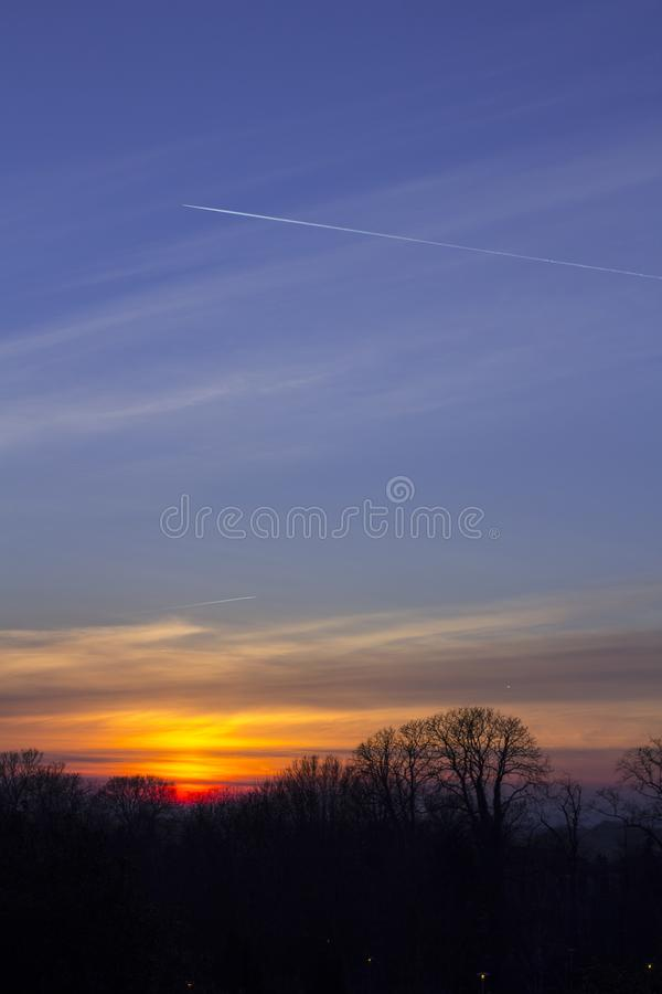 Trail from an airplane in the sky to sunset stock image