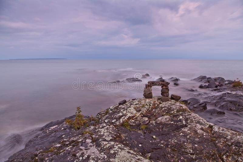Trail cairn on the rocky Lake Superior shore. Warm summer evening at Lake Superior. Trail cairn on missy royalty free stock images