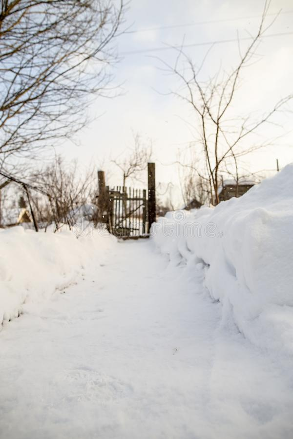 A trail cleared of snow leads to an old, rickety wicket and fence, on a frosty winter day in the countryside. stock photo