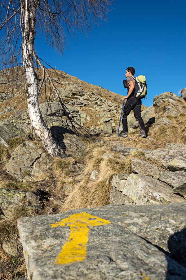 Trail direction indicator with mountaineer ascending to the top.   Conceptual stock image