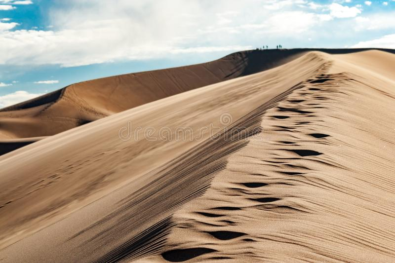 Trail of footprints climbs upward in the Great Sand Dunes. National Park in Colorado stock image