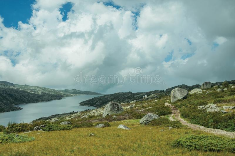 Trail going through rocky terrain with bushes and lake royalty free stock images