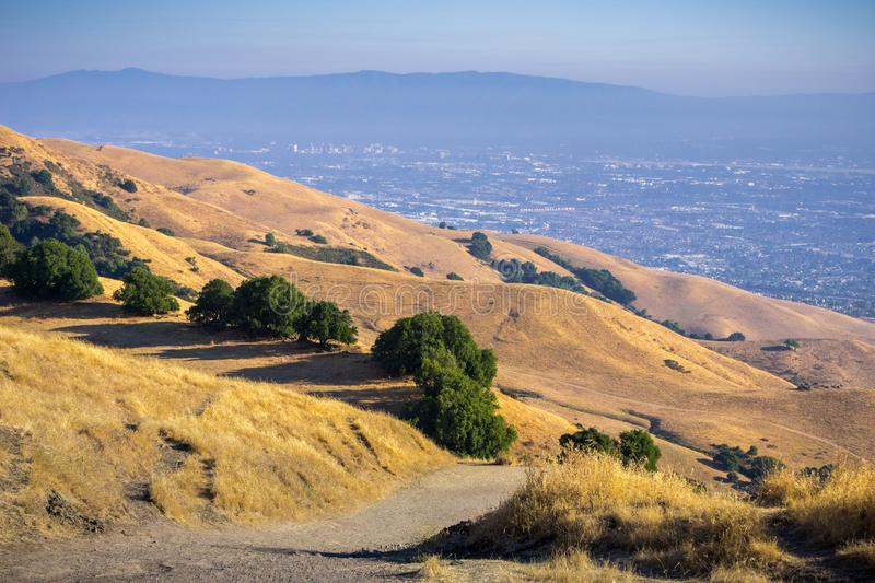 Trail through the golden hills of Mission Peak preserve; downtown San Jose in the background, south San Francisco bay, California stock photography