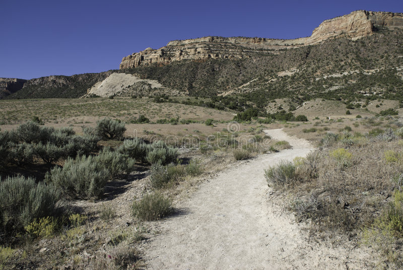 Trail in the high desert. Liberty Cap Trail in the Colorado National Monument near Grand Junction with mesas in the background and tipped sedimentary layers stock image