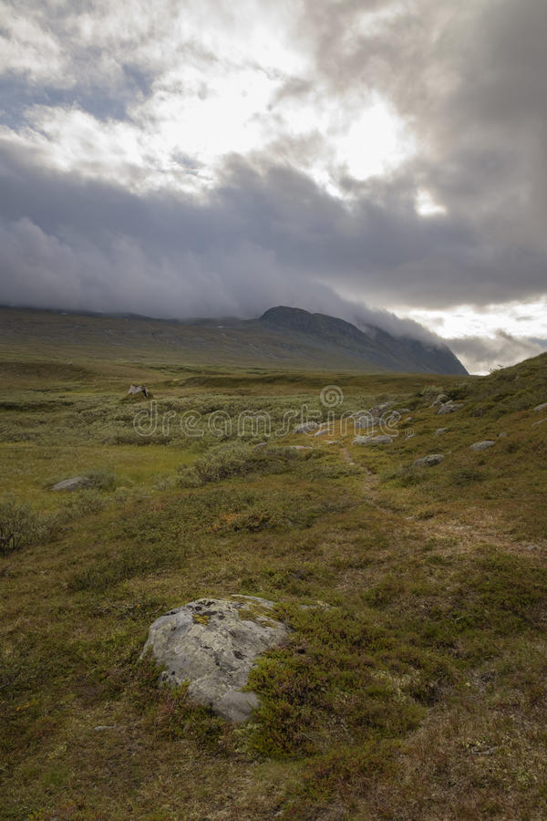 Trail leading to ancient Sami shelter in a desolate and overcast landscape royalty free stock photos