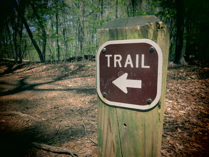 Trail Marker. A filtered photo of a trail marker sign with an arrow pointing to the correct direction stock photography