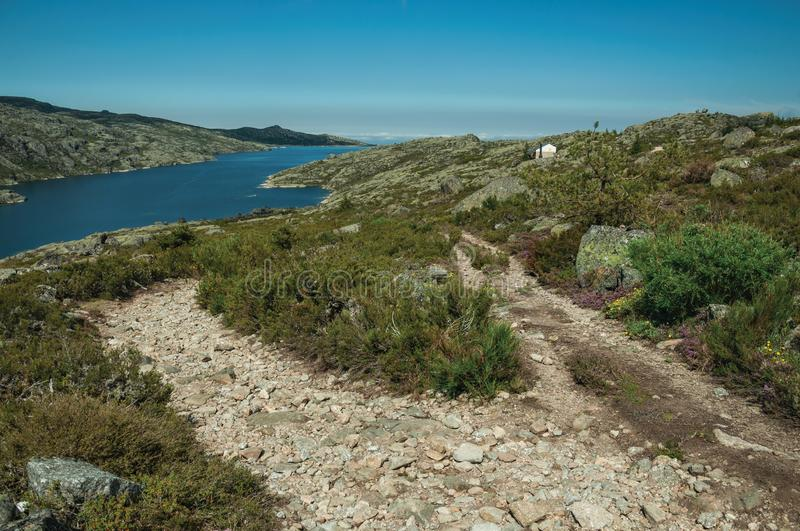 Trail over rocky terrain and lake on highlands stock photo