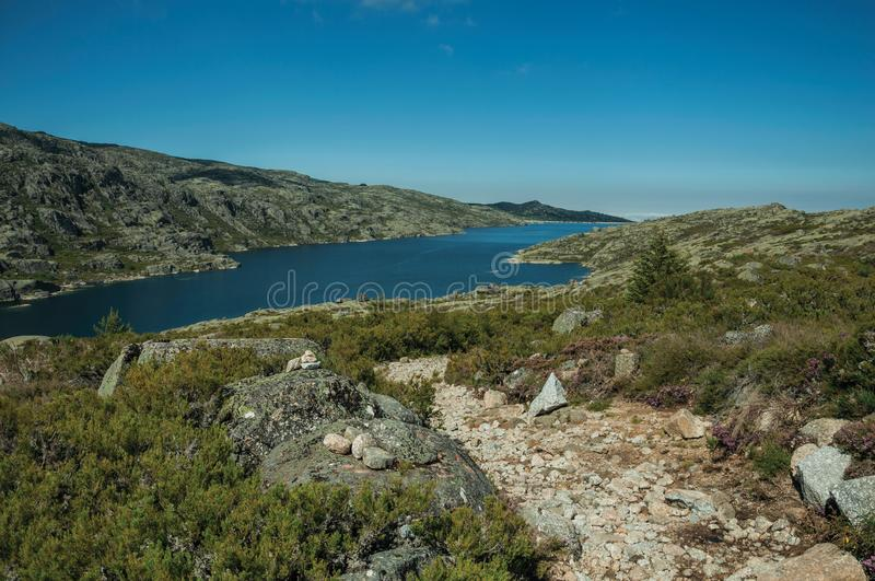 Trail over rocky terrain and lake on highlands stock photography