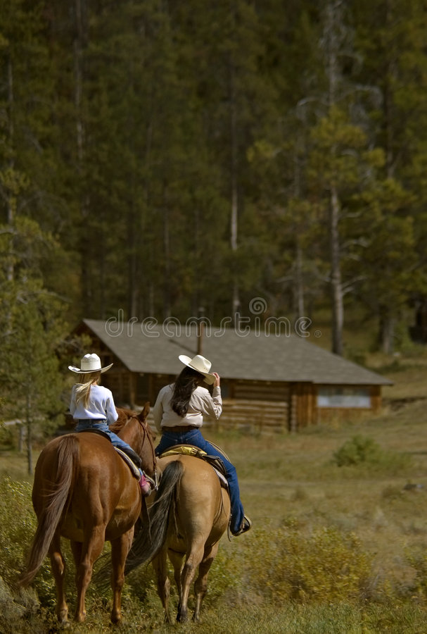 Trail Ride. Woman and little girl head out on trail ride royalty free stock images