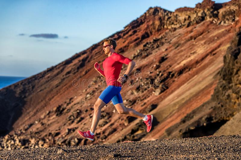 Trail run. Sport athlete runner man running in mountain nature background. Fitness motivation, fit person training body in rocky royalty free stock photography