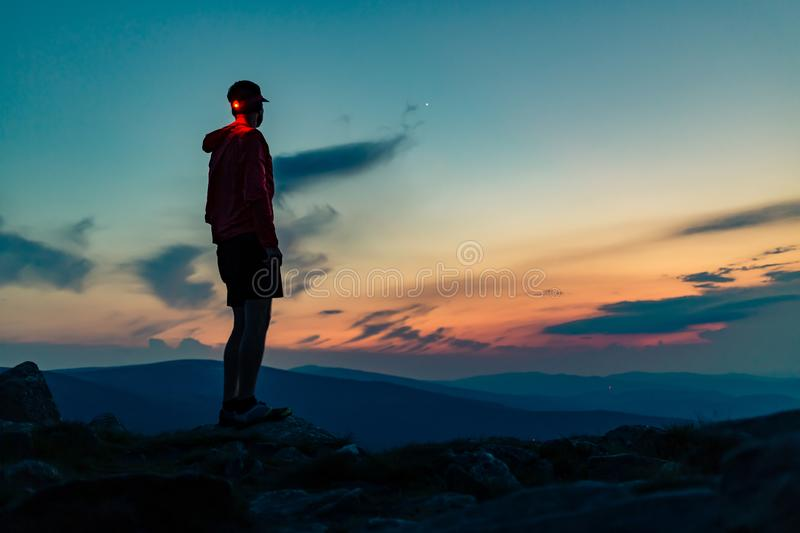 Trail runner with head lamp on top of mountain peak at night royalty free stock image