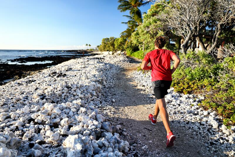 Trail runner jogging on running path at beach in white coral rocks at hawaii travel destination. Male athlete from. Behind doing cardio exercise outdoors in royalty free stock photo
