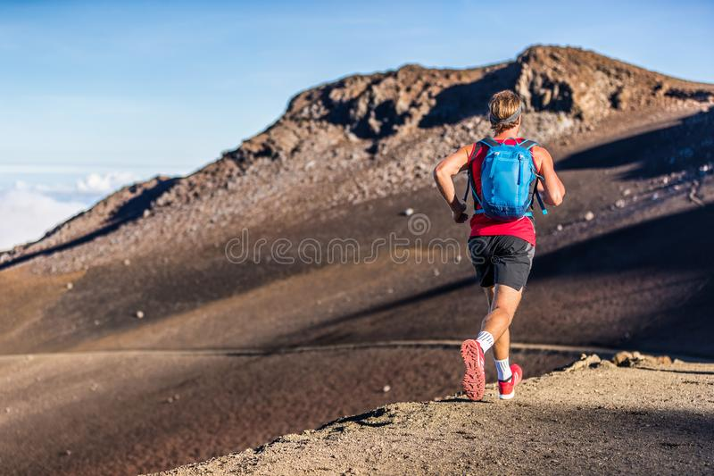 Trail runner man running with backpack on volcano mountain. Ultra marathon race athlete on volcanic path run in mountains. Landscape royalty free stock photos