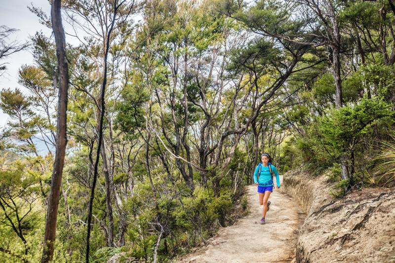 Trail runner woman running in forest nature path outdoors. Sport athlete girl training outdoor on adventure travel. Ultra run. Marathon workout stock images