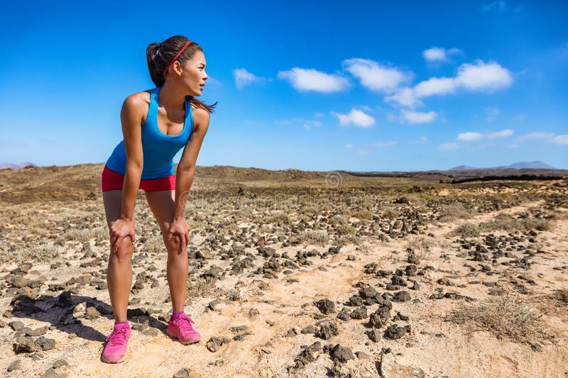 Trail runner woman tired breathing hard during ultra running cardio exercise exhausted on difficult run race. Asian young athlete. In desert summer heat stock photo