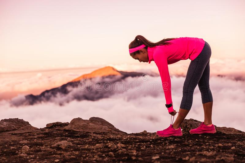 Trail runner woman tying running shoes laces getting ready to run on mountains nature in summer sunset dusk landscape. Nature. Outdoors stock photos