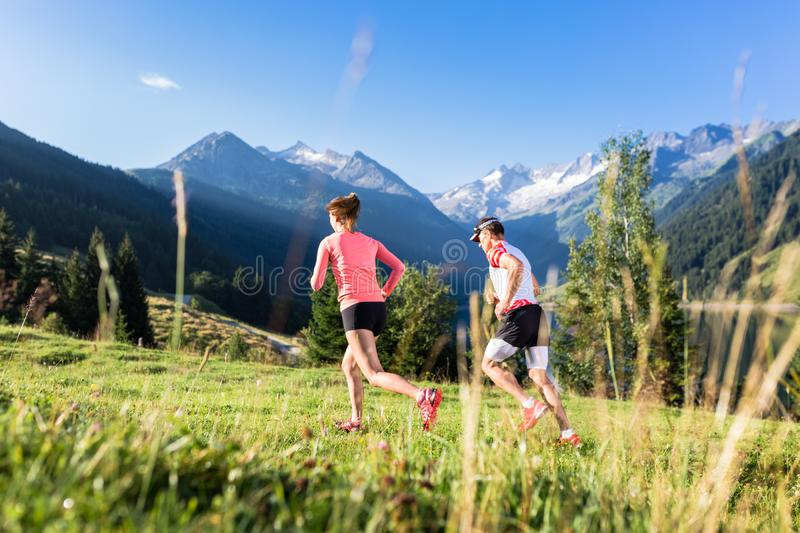 Trail runners running and training in the hills and mountains of the Alps in Europe, running towards a steep and snowy mountain royalty free stock image
