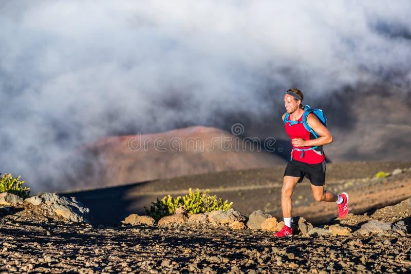 Trail running runner man on endurance run with backpack on volcano mountain. Ultra marathon race athlete on volcanic rocks path in stock photos