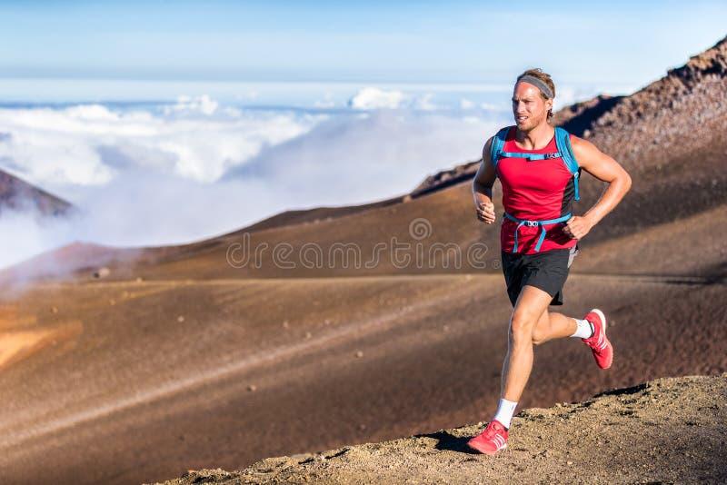 Trail running runner man on endurance run with backpack on volcano mountain. Ultra marathon race athlete on volcanic rocks path in stock image